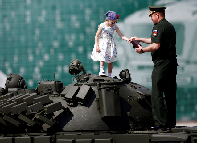 A Russian serviceman stands with a girl on top of a T-72 tank on display during the opening ceremony of the International Army Games 2017 in Alabino, outside Moscow, Russia, July 29, 2017. (Photo by Maxim Shemetov/Reuters)