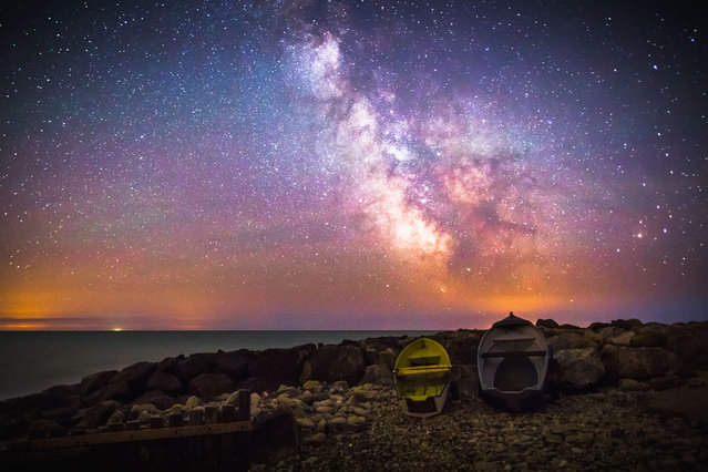 The galactic core of the milky way occupied by two small wooden boats on July 2, 2014, in Isle of Wight, UK. The Milky Way shines in mesmerizing colourful patterns above the Isle of Wight in stunning photographs. (Photo by Chad Powell/Barcroft Media)