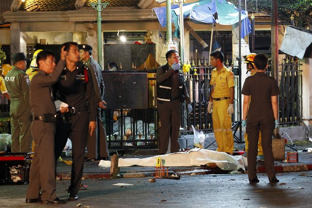 The body of a victim is covered with white sheet as security forces and emergency workers gather at the scene of the blast in central Bangkok August 17, 2015. (Photo by Kerek Wongsa/Reuters)