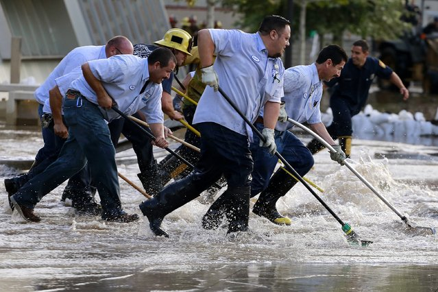 Workers push water on the UCLA campus, which was flooded by a broken thirty inch water main in the Westwood section of Los Angeles July 29, 2014. (Photo by Jonathan Alcorn/Reuters)