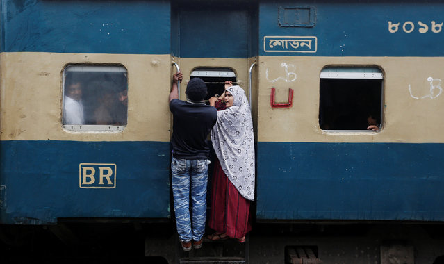 A couple stands on the steps of an overcrowded passenger train as they travel home to celebrate Eid al-Fitr festival, which marks the end of the Muslim holy fasting month of Ramadan, at a railway station in Dhaka, Bangladesh, July 5, 2016. (Photo by Adnan Abidi/Reuters)