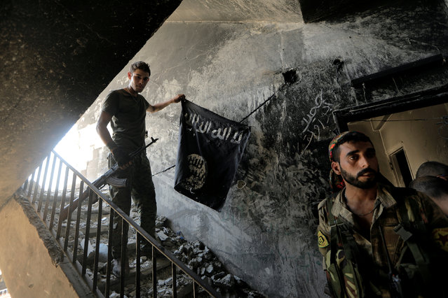 A member of the Syrian Democratic Forces calls his comrades during the fighting with Islamic State fighters in Raqqa, Syria August 14, 2017. (Photo by Zohra Bensemra/Reuters)
