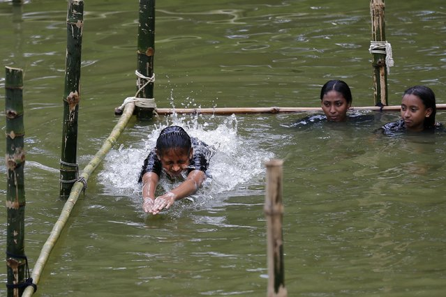 In this July 14, 2017 photo, a Bangladeshi girl jumps from the starting block as she attends a swimming training session at a pond in the Shishu Polli Plus area in Sreepur village, near Dhaka, Bangladesh. (Photo by A.M. Ahad/AP Photo)
