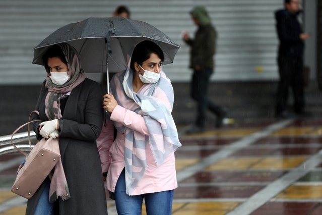 Iranian women wear protective masks to prevent contracting coronavirus, as they walk in the street in Tehran, Iran on February 25, 2020. (Photo by Nazanin Tabatabaee/WANA (West Asia News Agency) via Reuters)