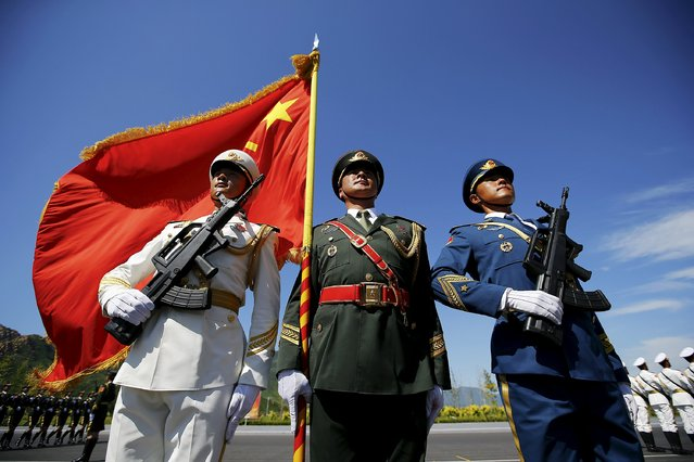 Officers and soldiers of China's People's Liberation Army hold a flag and weapons during a training session for a military parade to mark the 70th anniversary of the end of World War Two, at a military base in Beijing, China, August 22, 2015. (Photo by Damir Sagolj/Reuters)