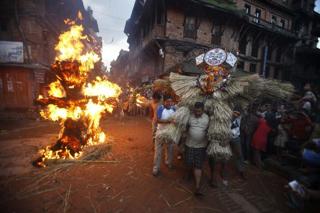 "People carry an effigy of demon Ghantakarna as another effigy of the demon is burnt to symbolize the destruction of evil, during the Ghantakarna festival in the ancient city of Bhaktapur on July 17, 2012. According to legend, the demon is believed to ""steal"" children and women from their homes and localities. (Photo by Navesh Chitrakar/Reuters Photo)"