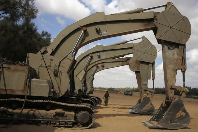 An Israeli soldier walks next to army excavators at a staging area near the border with the Gaza Strip August 4, 2014. Palestinians accused Israel of breaking its own ceasefire on Monday by launching a bomb attack on a refugee camp in Gaza City that killed an eight-year-old girl and wounded 29 other people. An Israeli military spokeswoman said she was checking the report. (Photo by Baz Ratner/Reuters)