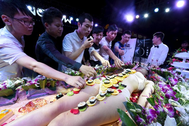 People eat sushi off the body of a model at an opening event of a bar in Taiyuan, Shanxi province, August 22, 2015. (Photo by Reuters/Stringer)