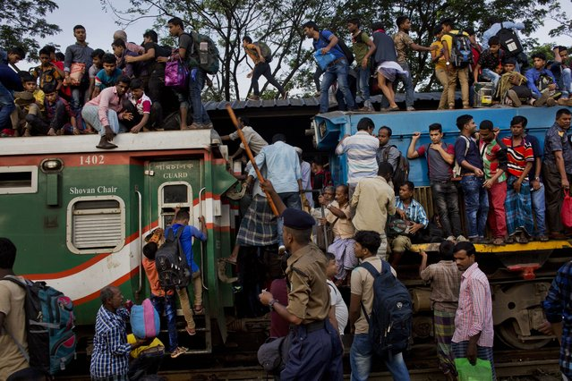 Bangladeshi Muslims climb onto the roof of an overcrowded train to travel to their hometowns ahead of of Eid al-Adha in Dhaka, Bangladesh, Friday, September 1, 2017. (Photo by Bernat Armangue/AP Photo)