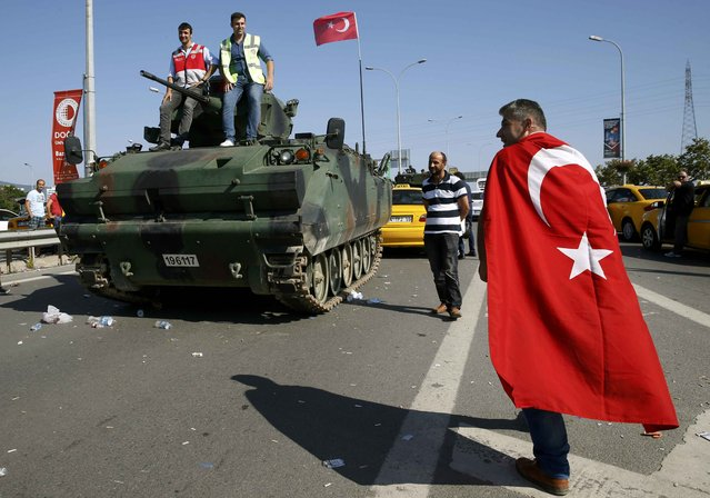 A man wrapped in a Turkish flag walks past a military vehicle in front of Sabiha Airport, in Istanbul, Turkey July 16, 2016. (Photo by Baz Ratner/Reuters)