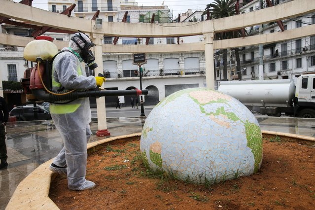 A worker wearing a protective suit disinfects a globe-shaped public garden, following the outbreak of coronavirus disease (COVID-19), in Algiers, Algeria on March 23, 2020. (Photo by Ramzi Boudina/Reuters)