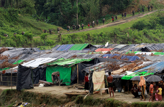 Rohingya refugees stand outside their temporary shelters at no man's land between Bangladesh-Myanmar border, as Myanmar security forces walk past a fence in Maungdaw, Myanmar September 9, 2017. (Photo by Danish Siddiqui/Reuters)
