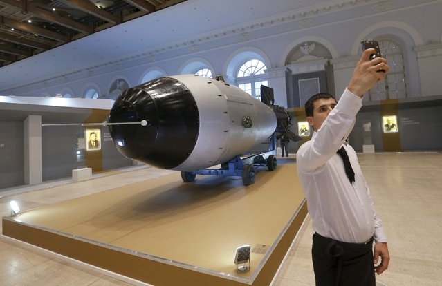 A man takes a selfie in front of a shell, which is the replica of the biggest detonated Soviet nuclear bomb AN-602 (Tsar-Bomb), in Moscow, Russia, August 31, 2015. (Photo by Maxim Zmeyev/Reuters)