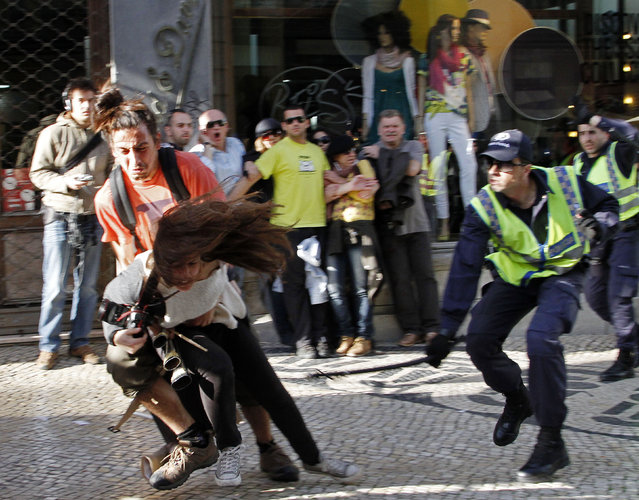 A policeman strikes AFP photojournalist Patricia Melo during the Portuguese general strike in Lisbon March 22, 2012. (Photo by Hugo Correia/Reuters)