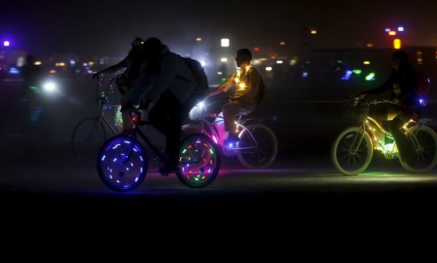 "Participants illuminate their bikes for travel at night on the Playa during the Burning Man 2015 ""Carnival of Mirrors"" arts and music festival in the Black Rock Desert of Nevada, September 1, 2015. (Photo by Jim Urquhart/Reuters)"