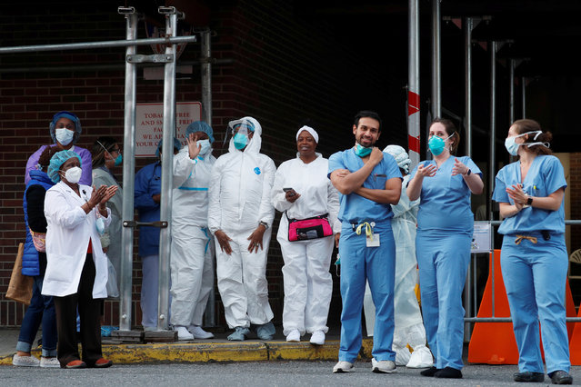 Healthcare workers at the Brooklyn Hospital Center react as residents and members of the New York City Fire Department (FDNY) cheer at 7:00pm amid the coronavirus disease (COVID-19) outbreak, in the Brooklyn borough of New York City, U.S., April 20, 2020. (Photo by Lucas Jackson/Reuters)