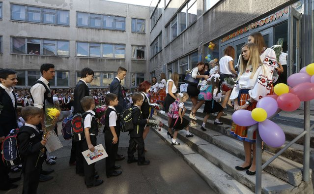 Students file in through the entrance to start their classes in a school in the southern coastal town of Mariupol, September 1, 2014. (Photo by Vasily Fedosenko/Reuters)
