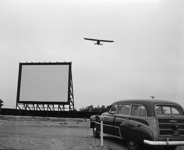 A plane comes in for a landing over the movie screen at the Fly-In Drive-In Theater in Farmingdale, N.J., July 20, 1951. The idea of combining fly-in facilities with drive-in parking space originated with Ed Brown, a World War II Navy flier and owner of an airport in Farmingdale. Movie- bound planes land at the airport, then taxi a few hundred feet down a special runway to the theater. Fliers come to the theater from a radius of a hundred miles, according to Brown. (Photo by Ed Ford/AP Photo)