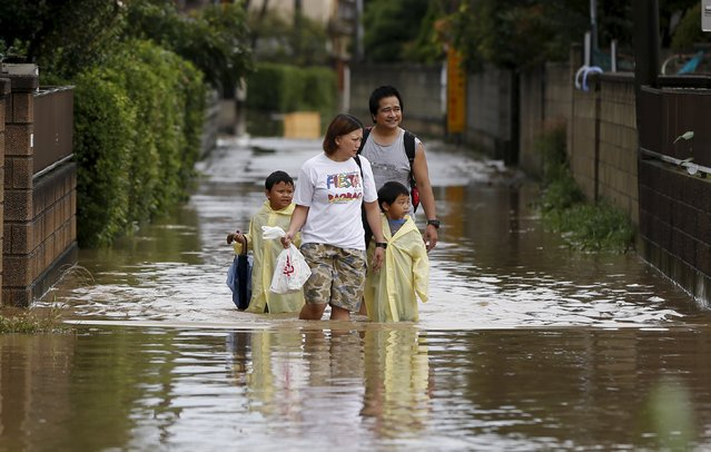 A family wades through a residential area flooded by the Kinugawa river, caused by typhoon Etau, in Joso, Ibaraki prefecture, Japan, September 10, 2015. (Photo by Issei Kato/Reuters)