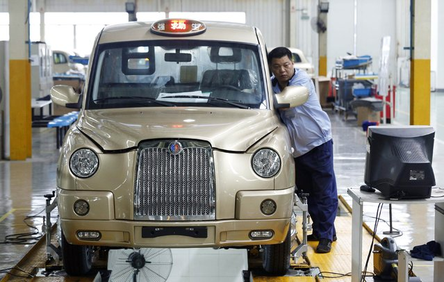 """A worker inspects a newly-made Geely Englon TX4 taxi, a recreation of the """"London cab"""", at a Geely Englon factory in Shanghai, September 17, 2014. Qiangsheng, Shanghai's largest taxi company, ordered a first batch of 50 Geely Englon TX4 taxis, which could hit the Shanghai streets as early as October this year. The China-made """"London cabs"""" are painted in champagne gold colour, instead of the well-known black, local media reported. (Photo by Reuters/Stringer)"""