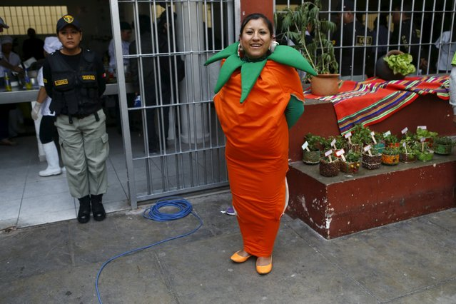 "An inmate, dressed as a carrot, participates in a culinary competition at the Santa Monica female prison in Lima, September 10, 2015. About 14 prisoners from different jails took on the roles of cooks and assistants to participate in a culinary competition called ""Inpe Mistura 2015"", an event held concurrently with the Mistura food fair taking place in Lima in September. (Photo by Mariana Bazo/Reuters)"