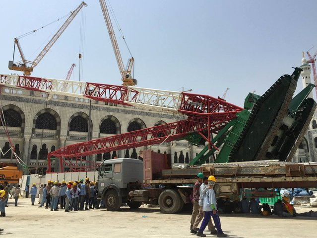 Workers walk near a construction crane which crashed in the Grand Mosque in the Muslim holy city of Mecca, Saudi Arabia September 12, 2015. (Photo by Mohamed Al Hwaity/Reuters)