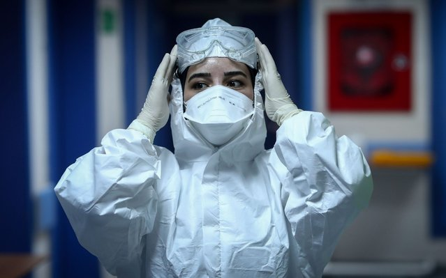 A medical worker wearing Personal Protective Equipment (PPE) adjusts her gear at the Istanbul Sisli Hamidiye Etfal Training and Research Hospital, in Istanbul, Turkey, 20 May 2020 (issued 22 May 2020). President Erdogan announced a curfew in 81 Turkish cities, including Istanbul, from 23 to 26 May 2020 to curb the spread of the coronavirus disease (COVID-19) pandemic. The lockdown coincides with the festival of Eid al-Fitr, which marks the end of the Muslim fasting month of Ramadan. (Photo by Sedat Suna/EPA/EFE)