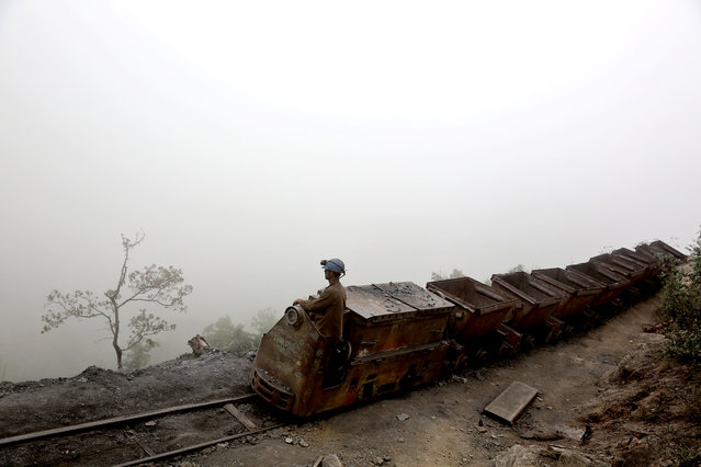 In this Thursday, May 8, 2014 photo, an Iranian coal miner moves wagons to be loaded with coal at a mine near the city of Zirab 212 kilometers (132 miles) northeast of the capital Tehran, on a mountain in Mazandaran province, Iran. International sanctions linked to the decade-long dispute over Iran's nuclear program have hindered the import of heavy machinery and modern technology in all sectors, and coal mining is no exception. (Photo by Ebrahim Noroozi/AP Photo)