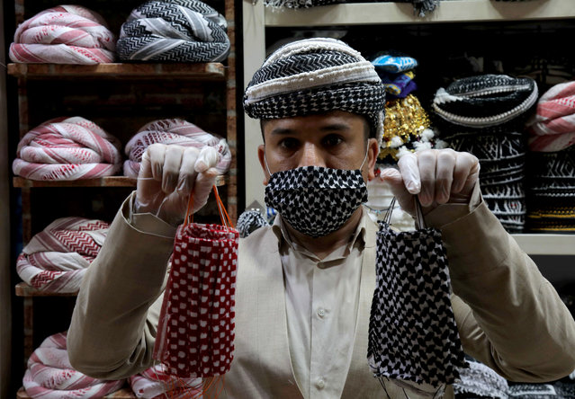 An Iraqi Kurdish man shows face masks made by a tailor with traditional checkered pattern fabric, in Arbil, the capital of the northern Iraqi Kurdish autonomous region, during the ongoing COVID-19 pandemic crisis, on June 18, 2020. (Photo by Safin Hamed/AFP Photo)