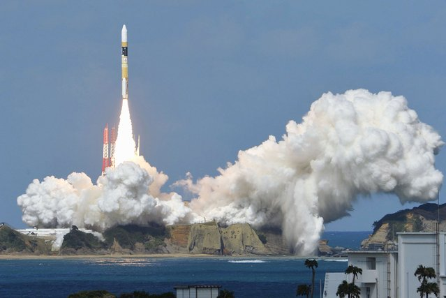 A H-IIA rocket carrying Himawari 8 weather satellite, blasts off from the launching pad at Tanegashima Space Center on the Japanese southwestern island of Tanegashima, in this photo taken by Kyodo October 7, 2014. (Photo by Reuters/Kyodo News)