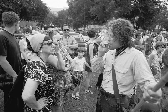 """An unidentified young man smokes what appears to be a marijuana cigarette for the benefit of a pair of middle-aged women, along with several other onlookers, during the """"Honor America Day Smoke-In"""" thrown by marijuana activists to protest the official """"Honor America Day"""" ceremonies being held at the Lincoln Memorial, Washington, DC, July 4, 1970. The Vietnam war sharply divided America in 1970, and supporters of Richard Nixon sought to counter the growing opposition by organizing a Fourth of July Honor America Day in Washington DC. The celebration was quickly crashed by thousands of its critics, with marijuana activists staging a """"smoke-in"""" to protest(Photo by David Fenton/Getty Images)"""