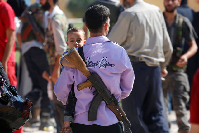 A rebel fighter carries a boy as civilians and rebels who were evacuated from the besieged Damascus suburb of Daraya, after an agreement reached on Thursday between rebels and Syria's army, arrive in the rebel-controlled city of Idlib August 27, 2016. (Photo by Ammar Abdullah/Reuters)