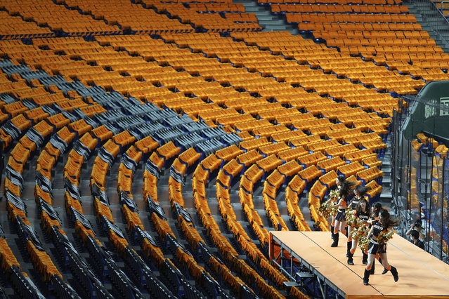 Cheer leaders perform to empty stands prior an opening baseball game between the Yomiuri Giants and the Hanshin Tigers at Tokyo Dome in Tokyo Friday, June 19, 2020. After a three-month delay caused by the coronavirus pandemic, the world's second-most famous baseball league opened a shortened season Friday without the presence of fans. (Photo by Eugene Hoshiko/AP Photo)