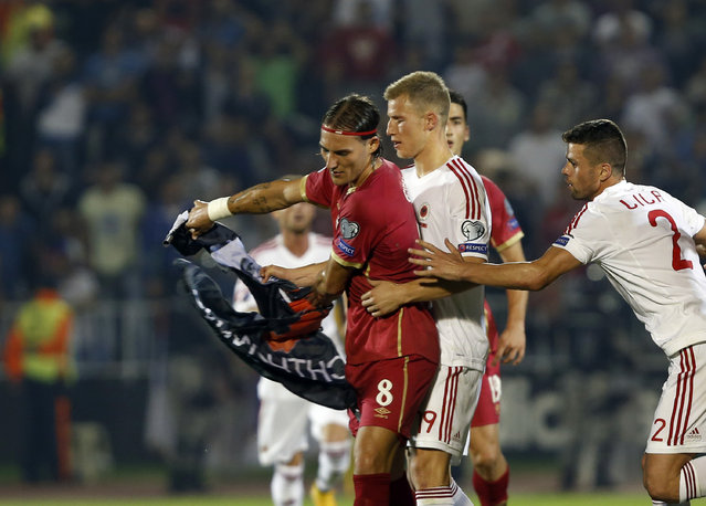 Serbia's Nemanja Gudelj, left, holds a flag as he and Albania's Bekim Balaj, centre, clash during the Euro 2016 Group I qualifying match between Serbia and Albania, at the Partizan stadium in Belgrade, Serbia, Tuesday, October 14, 2014. (Photo by Darko Vojinovic/AP Photo)