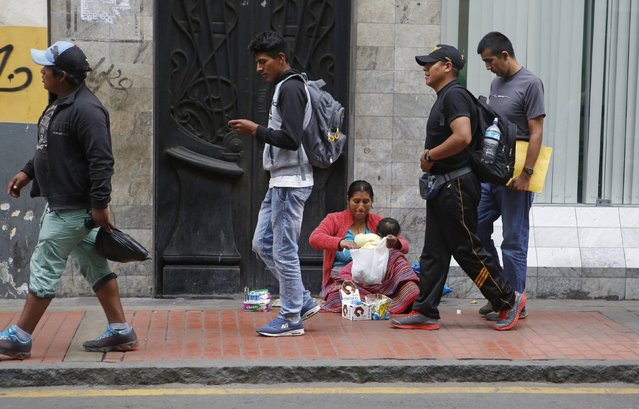 People walk past a street vendor selling candies in downtown Lima, September 23, 2015. (Photo by Mariana Bazo/Reuters)