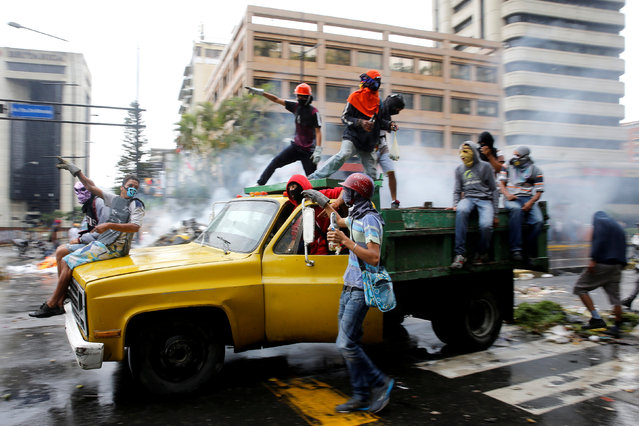 """Demonstrators ride on a truck while rallying against Venezuela's President Nicolas Maduro's government in Caracas, Venezuela, June 29, 2017. Ivan Alvarado: """"This was one of the last really big rallies, and the number of protestors coming out on the streets started to decrease. The protesters used trucks to make barricades and block the streets in the Altamira area. This truck was being driven quite slowly, and I shot the image at a slow shutter speed panning to capture the sense of movement of the truck. I like the man standing on the top of the truck who looks like he is urging the group onto action"""". (Photo by Ivan Alvarado/Reuters)"""