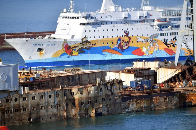 The wreck of cruise liner Costa Concordia is towed by five tugboats during its final journey inside the port of Genoa, Italy, 01 September 2016. The cruise liner, which capsized on 13 January 2012 off the Giglio Island, claiming 32 lives, will be scrapped at the dock of ship repairs in the port of Genoa. (Photo by Luca Zennaro/ANSA)