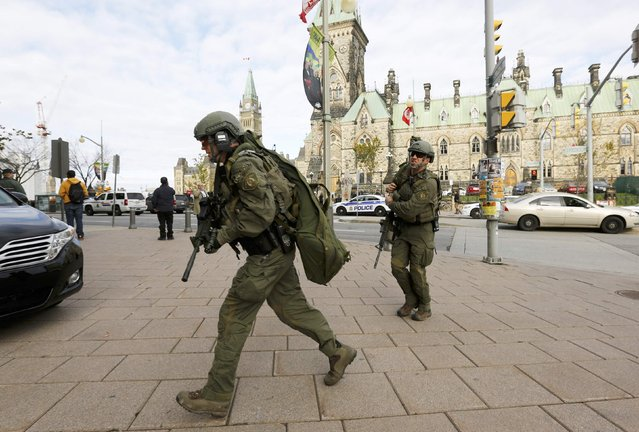 Armed RCMP officers head towards the Langevin Block on Parliament Hilll following a shooting incident in Ottawa October 22, 2014. A Canadian soldier was shot at the Canadian War Memorial and a shooter was seen running towards the nearby parliament buildings, where more shots were fired, according to media and eyewitness reports. (Photo by Chris Wattie/Reuters)
