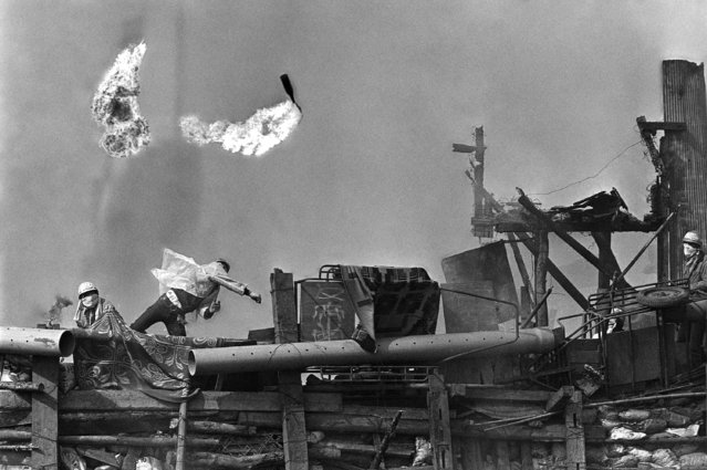 Japanese students hurl flaming Molotov cocktails at police, from a barricaded area they have built at the site of a proposed new airport, 60 miles from Tokyo, September 30, 1971. Fifty-two hundred leftist students and farmers opposed to the building of the airport fought pitched battles with police last month; three police men were killed, many injured. (Photo by Toichi Sakakibara/AP Photo)