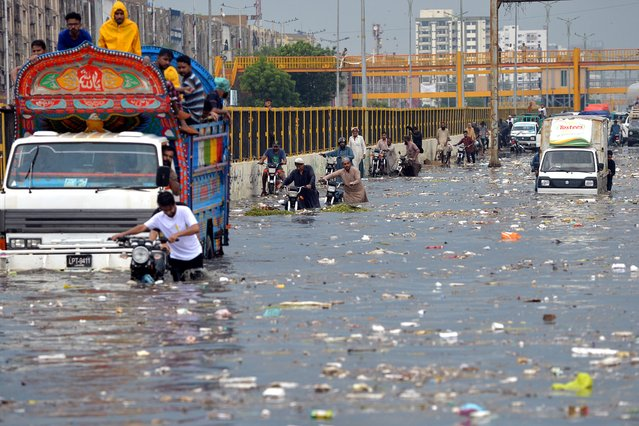 People wade through a flooded street after heavy monsoon rains in Karachi on July 26, 2020.   (Photo by Rizwan Tabassum/AFP Photo)
