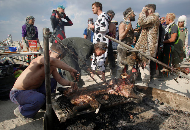 Participants roast a pig on the remains of the Man as approximately 70,000 people from all over the world gathered for the 30th annual Burning Man arts and music festival in the Black Rock Desert of Nevada, U.S. September 4, 2016. (Photo by Jim Urquhart/Reuters)