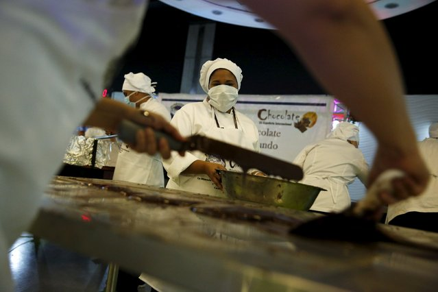 Workers spread chocolate out on a metal table to cool it off during an attempt to break the Guinness World Record for the biggest chocolate coin in Caracas, Venezuela, October 1, 2015. More than 80 people will work with 100% Venezuelan cacao to create the coin that is estimated to weigh 1,000 kg, according to local media. (Photo by Carlos Garcia Rawlins/Reuters)