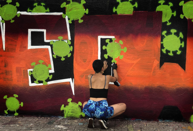 An artist sprays paints a wall with topic about the Coronavirus in Barcelona, Spain, Thursday, August 13, 2020. Spain's daily number of new COVID-19 cases has shot up, with almost 2,935 officially reported Thursday compared with 1,690 the previous day. (Photo by Emilio Morenatti/AP Photo)