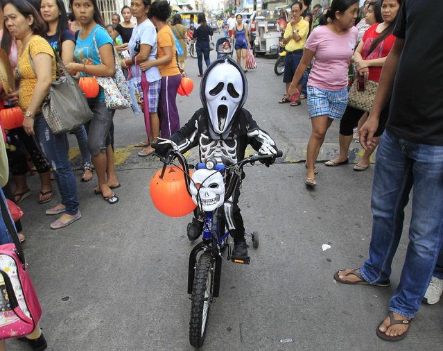 A school boy wearing a mask and a costume arrives on a bicycle before the start of a Halloween Parade along a street in Manila October 30, 2014. (Photo by Romeo Ranoco/Reuters)
