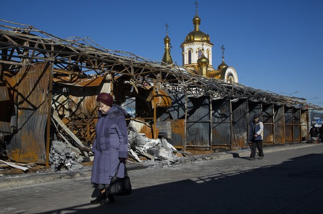 In this photo taken on Tuesday, October 28, 2014, people walk past a bombed out street market near the train station in the town of Donetsk, eastern Ukraine. (Photo by Dmitry Lovetsky/AP Photo)