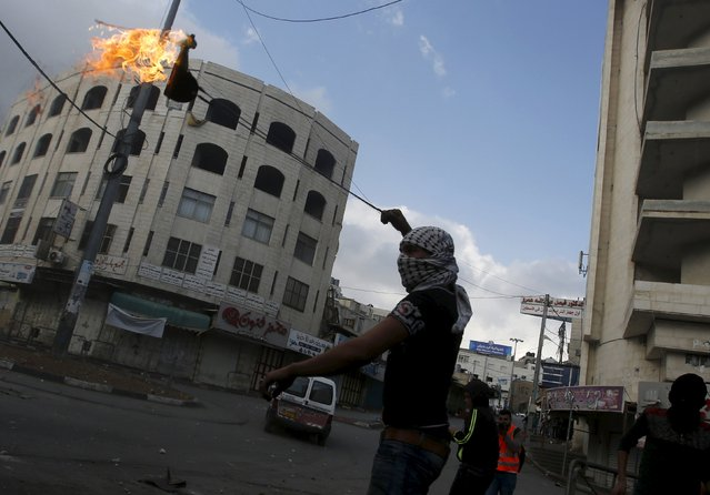 A masked Palestinian uses a sling to throw a molotov cocktail at Israeli troops during clashes in the West Bank city of Hebron October 9, 2015. (Photo by Mussa Qawasma/Reuters)