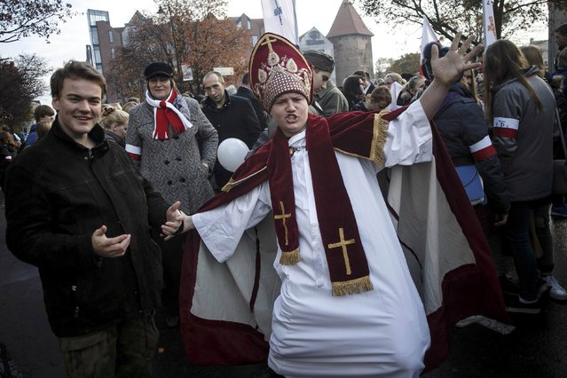 A man pose wearing a pope outfit during the Independence Day celebrations in Gdansk November 11, 2014. (Photo by Lukasz Glowala/Reuters/Agencja Gazeta)