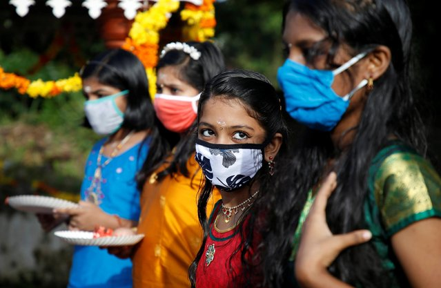 Girls wearing protective face masks wait to pray inside temple premises on the occasion of the annual harvest festival of Onam on the outskirts of Kochi, India, August 31, 2020. (Photo by Sivaram V/Reuters)