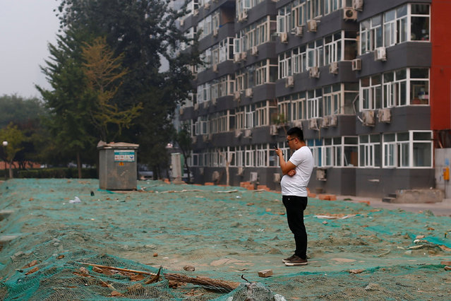 A man uses his phone as he stands in front of an apartment building in Beijing, China, September 16, 2016. (Photo by Thomas Peter/Reuters)