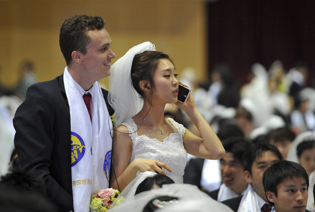 """A newly-married bride talks on the phone during a mass wedding of the Unification Church held in the church's headquarters in Gapyeong, east of Seoul, on February 17, 2013.  The Unification Church, set up by Sun Myung Moon in Seoul in 1954, is one of the world's most controversial religious organisations, and its devotees are often dubbed """"Moonies"""" after the founder. (Photo by Kim Jae-Hwan/AFP Photo)"""